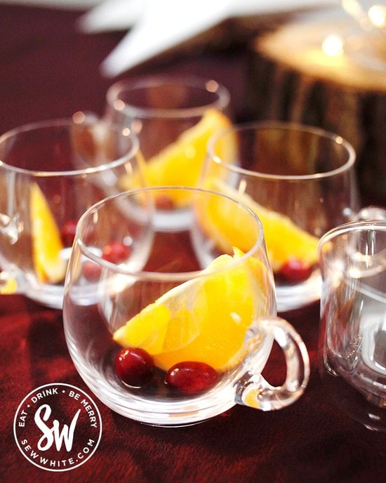 Glass punch glasses with a slice of orange and fresh cranberries in for a Christmas cocktail.