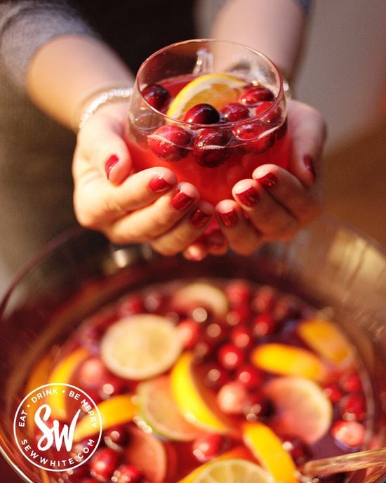 Two hands holding a Christmas Cranberry Punch glass cup with fresh cranberries and orange slice in.