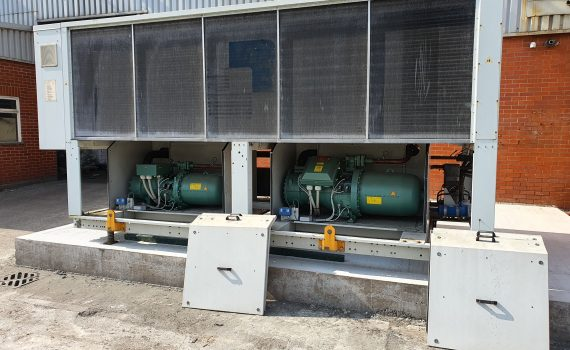 Large white chiller being inspected to compose a chiller maintenance schedule