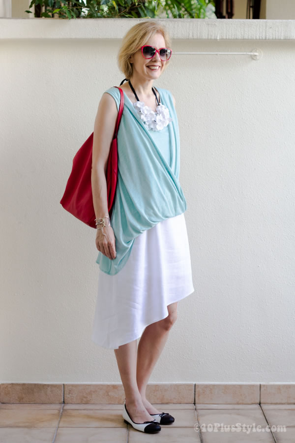 Asymmetrical dress with asymmetrical top and white flower necklace | 40plusstyle.com