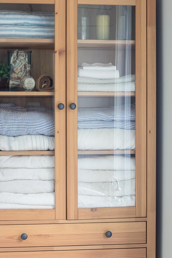 wood and glass linen cabinet coastal lake house master bathroom