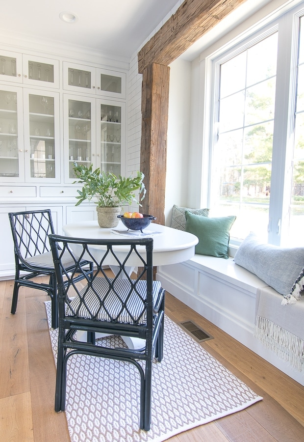 White breakfast nook with rustic beams and green pillows
