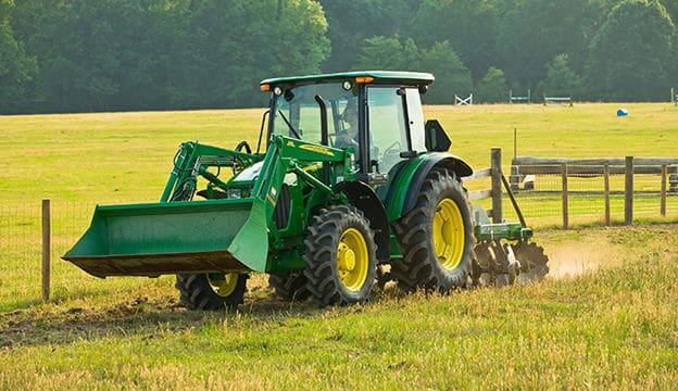 green farm tractor on a field
