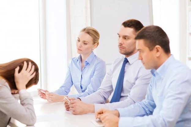 An employee sitting with her managers and holding her head in distress as she gets fired from her job