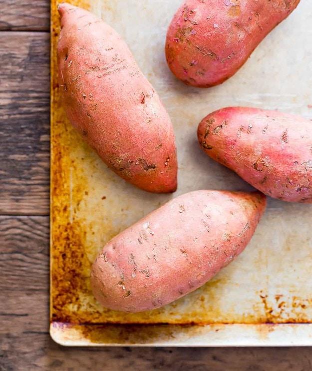 raw sweet potatoes on a sheet pan