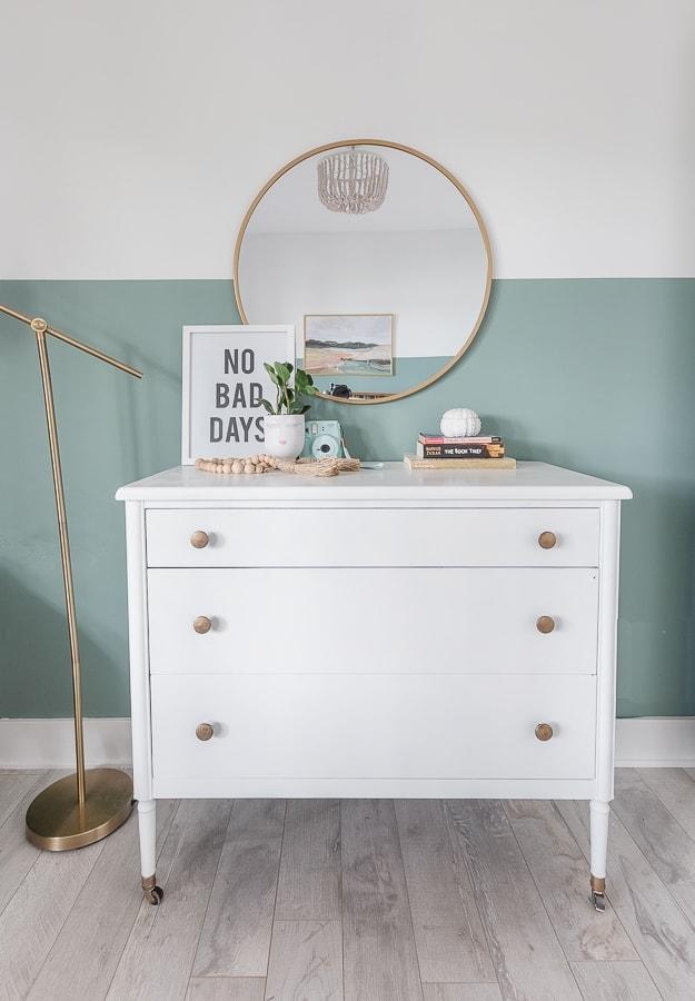 white dresser, brass accents, round mirror