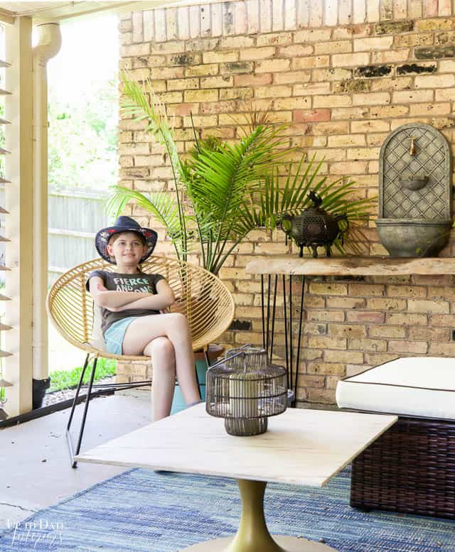 View of outdoor living room with girl sitting in a hair, palm tree, table with fountain and pale yellow bricks