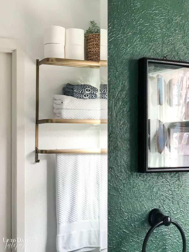 Bathroom Wall Decor Ideas, mirror reflecting gold shelf next to a green wall