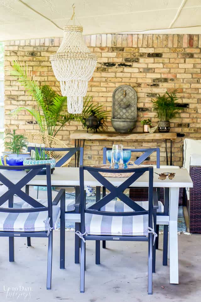 white dining table and wall fountain. Eclectic outdoor living space on back porch.
