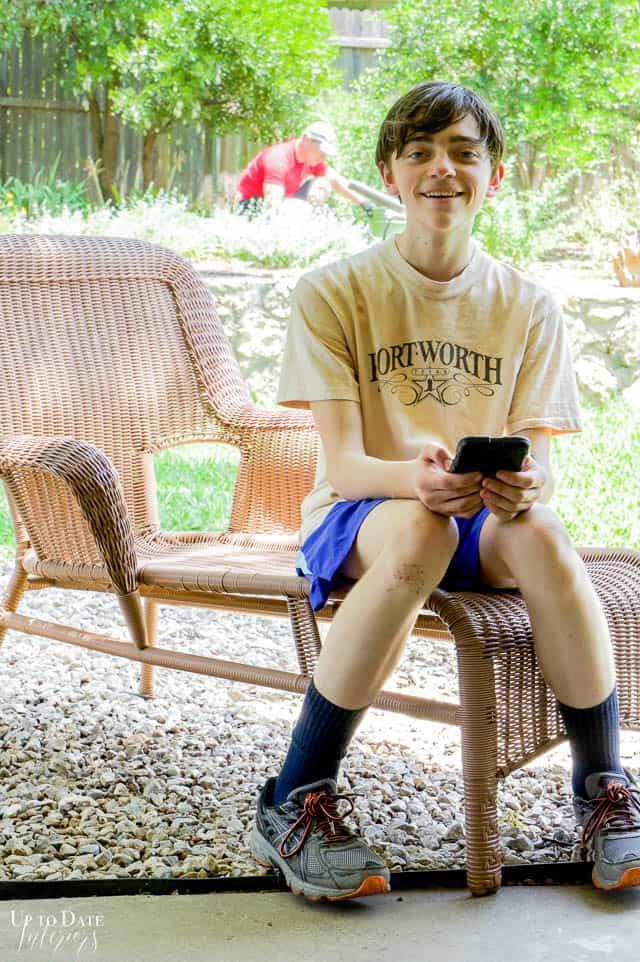 Boy sitting on outside wicker lounge chair