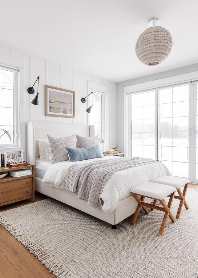 lake house bedroom. White walls, neutral bedding, warm wood floors.