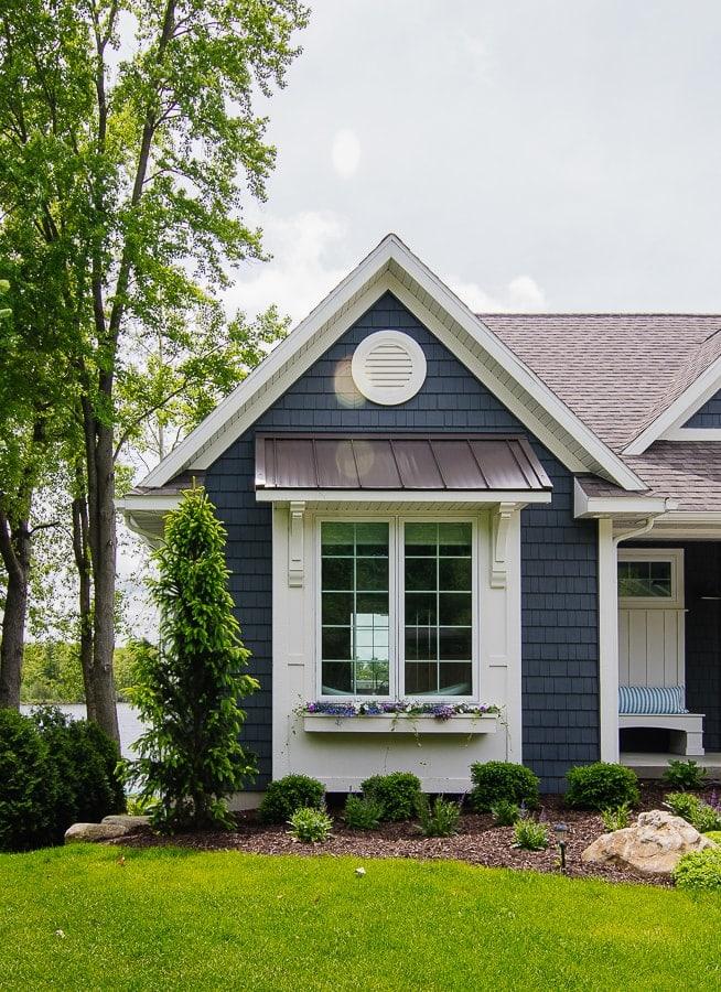 dark grey house exterior with white trim and pergola