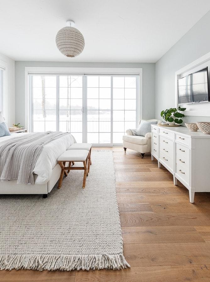 lake house bedroom large sliding double doors, light blue walls, wood flooring.