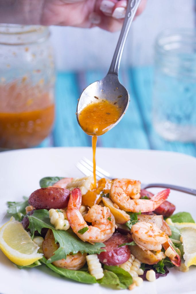 Lowcountry Boil Salad being drizzled with Old Bay Vinaigrette