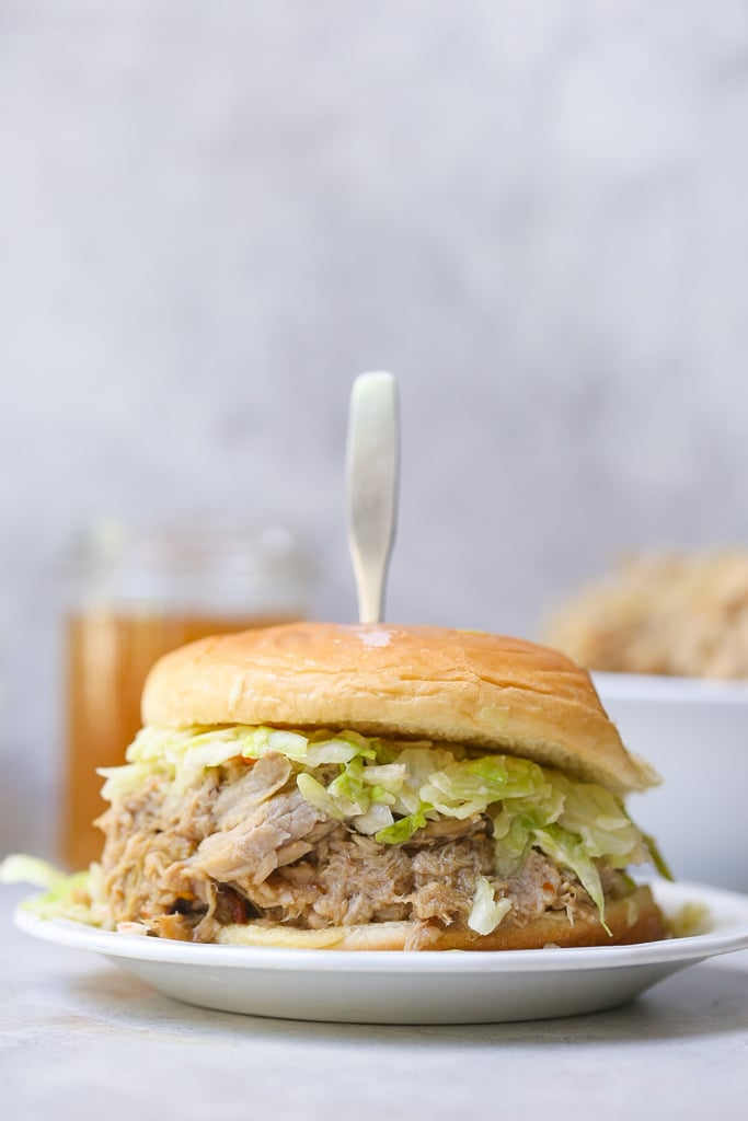 Carolina pulled pork sandwich on white plate with silver sandwich holder and green slaw