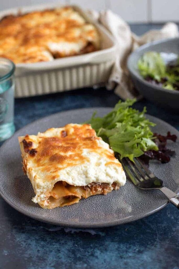 Effortless Foodie's Easy Lasagne served with a salad on a blue plate in the Winter Warming Oven Bakes CookBlogShare round up.