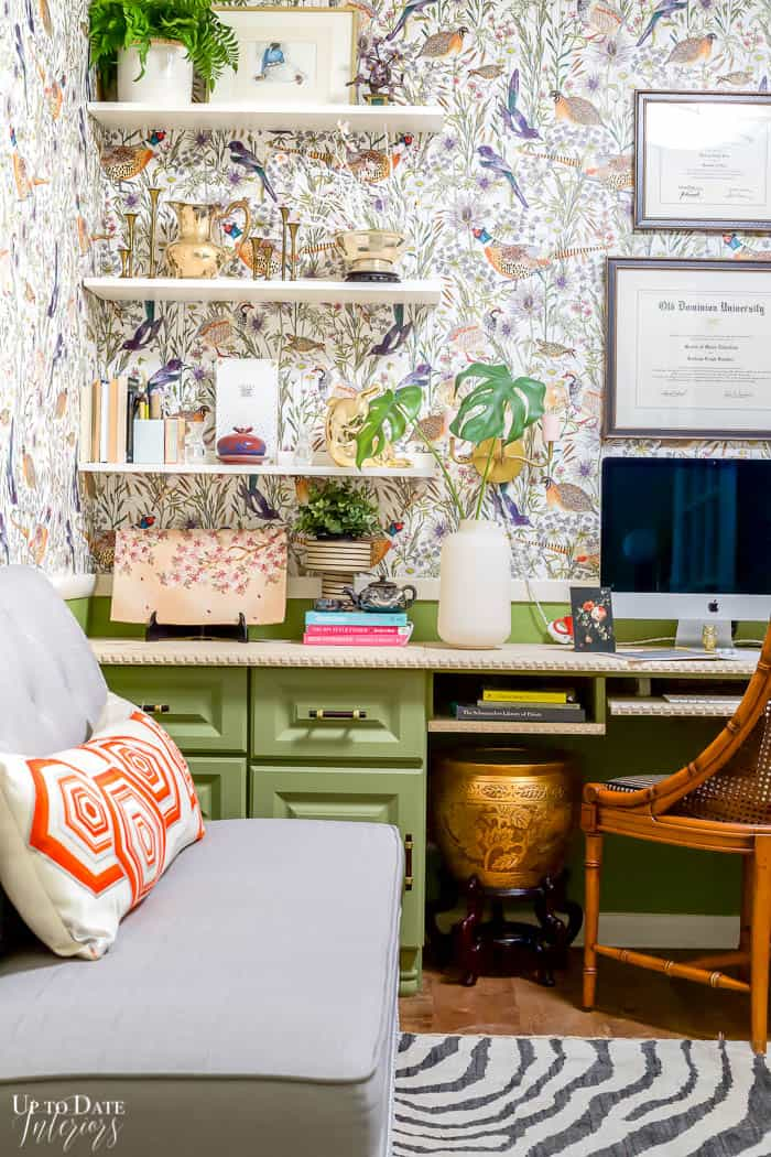 Open office shelves on bird wallpaper with green cabinets and a zebra rug.