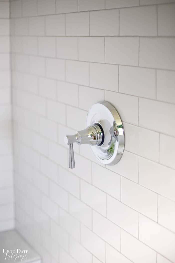 close up of a chrome shower faucet trim against a white subway tile surround.