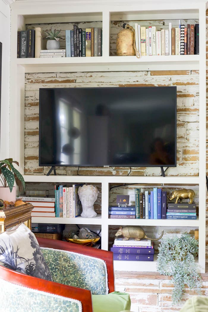 Built in bookcase with colorful books, brass figures, bust, large tv, and a green chair in front.