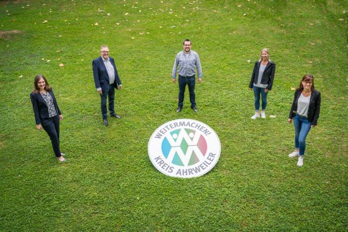 Das Foto zeigt von links nach rechts die Abteilungsleiterin der Abteilung 4.6 Jennifer Nehring, Landrat Dr. Jürgen Pföhler, Projektleiter Mario Stratmann und Projektmitarbeiterinnen Michaela Wolff und Antje Weber. Diese stehen um das Projektlogo.