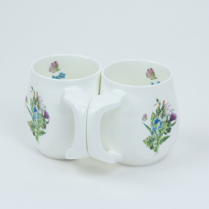 Two white fine bone china mugs with a colourful butterfly printed on the side.