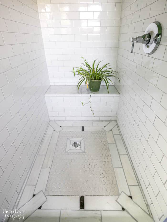 Shower surround with art decor pattern on the floor with white and black marble.