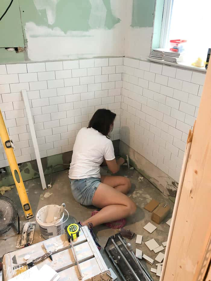 woman install white subway tile in a small bathroom White And Grey Bathroom