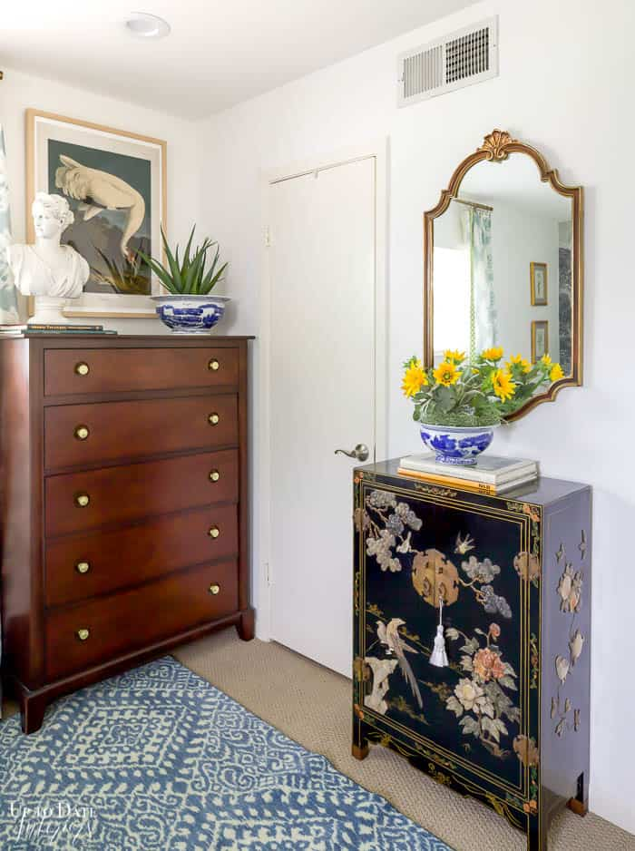 Corner of bedroom with tall brown dresser and black asian cabinet decorated with plants, books, and a bust.  Wall art and gold mirror on the walls.
