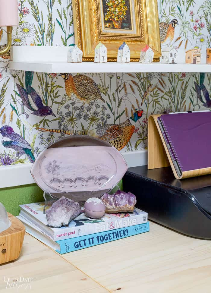 Art, pottery, and books styled in an eclectic and colorful office.