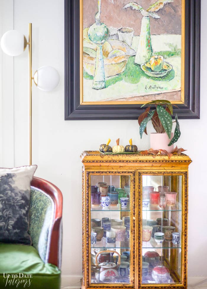green painting with glass and gold cabinet holding Japanese pottery next to green chair.