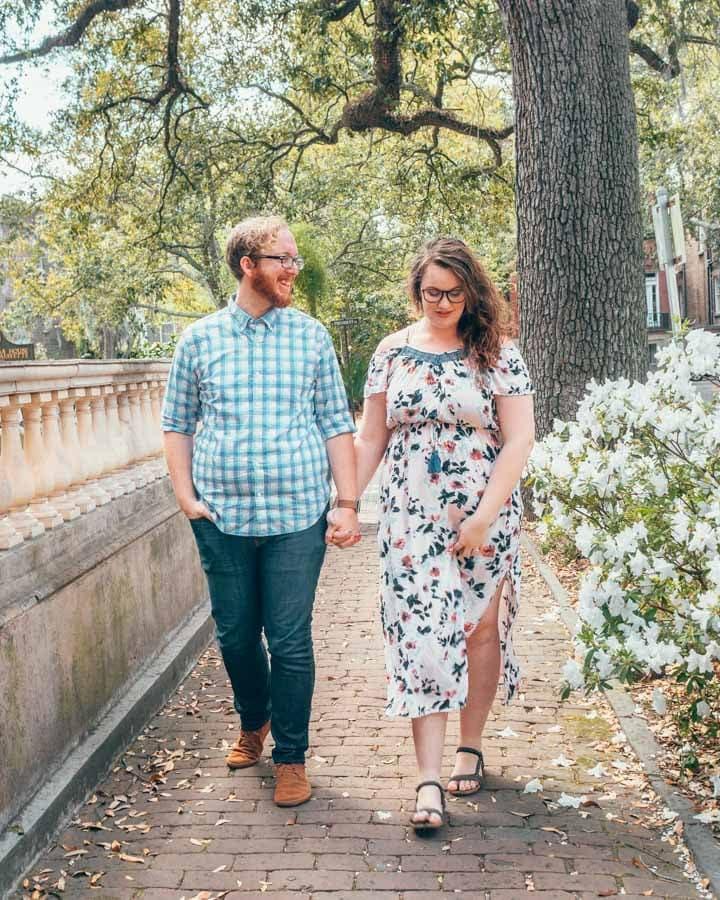 Couple walking hand in hand through Savannah in the springtime next to a blooming azalea bush.