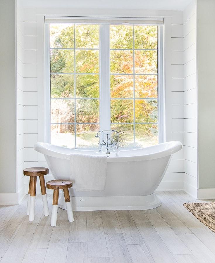white and blue coastal master bathroom free standing tub and wood stools