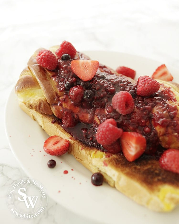 Brioche Bread Pudding covered in hot fruit compote and fresh berries