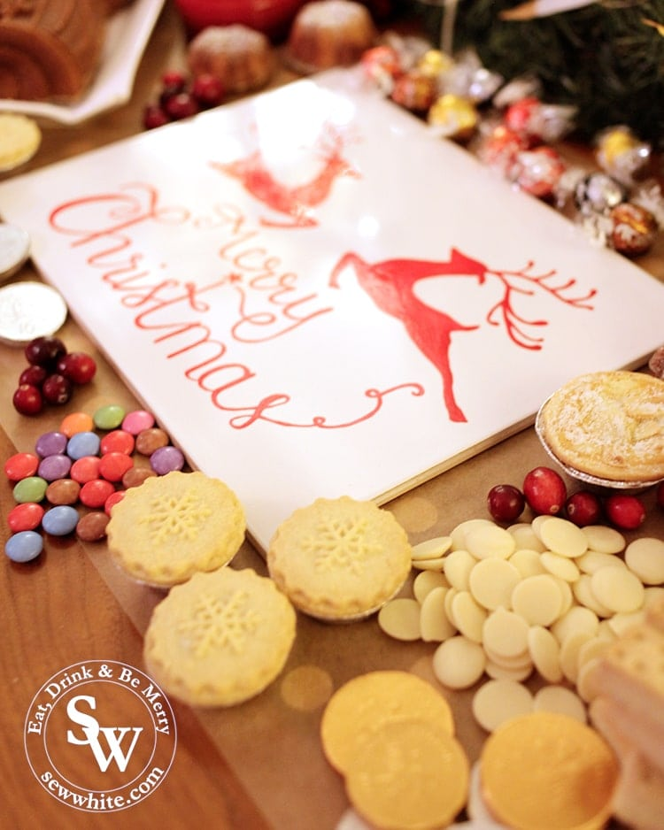 Close up of mince pies, chocolate buttons, fresh cranberries and smarties with a merry christmas sign.