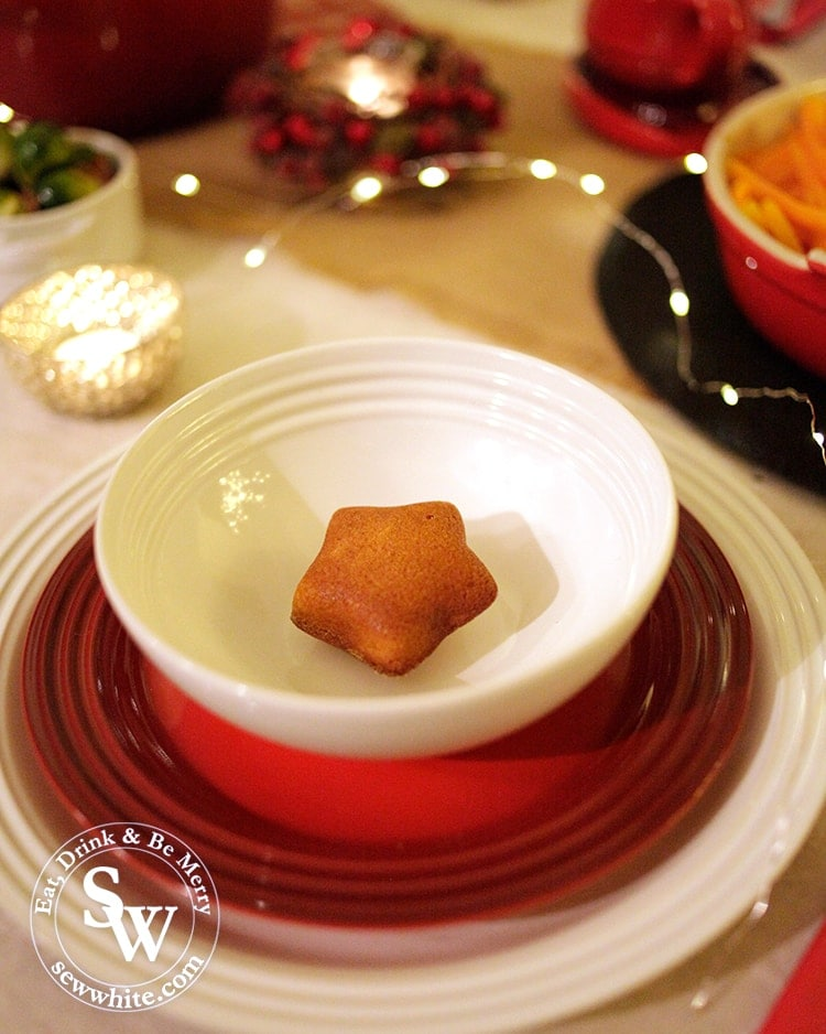 Christmas place setting with Le Creuset red and white plates.