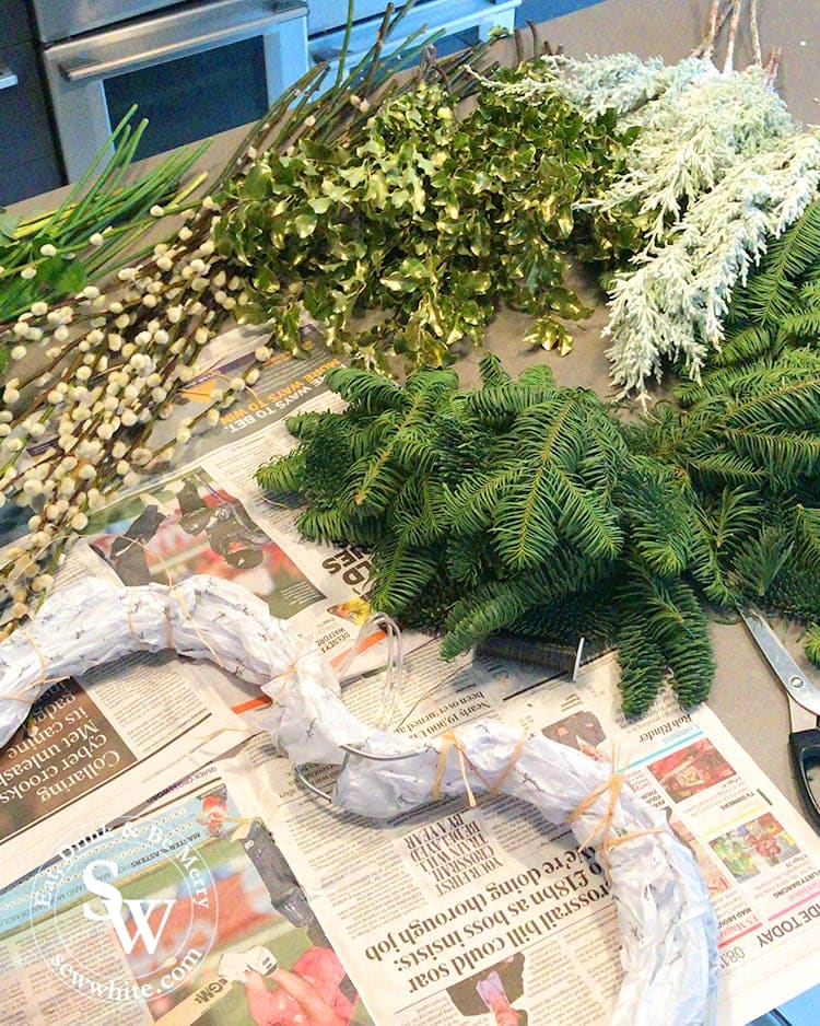 Kitchen table filled with everything needed for wreath making.