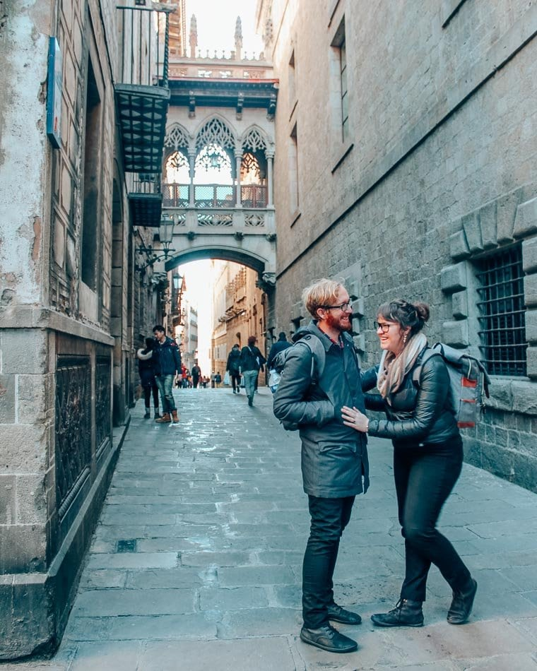 Couple wearing backpacks in front of a bridge above an alley in Barcelona, Spain.
