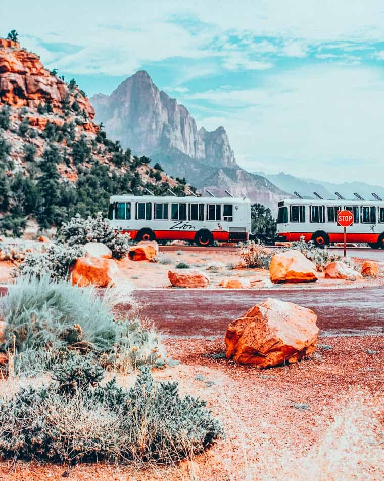 The Zion National Park Shuttle parked at a stop, with the looming cliffs of Zion in the background.