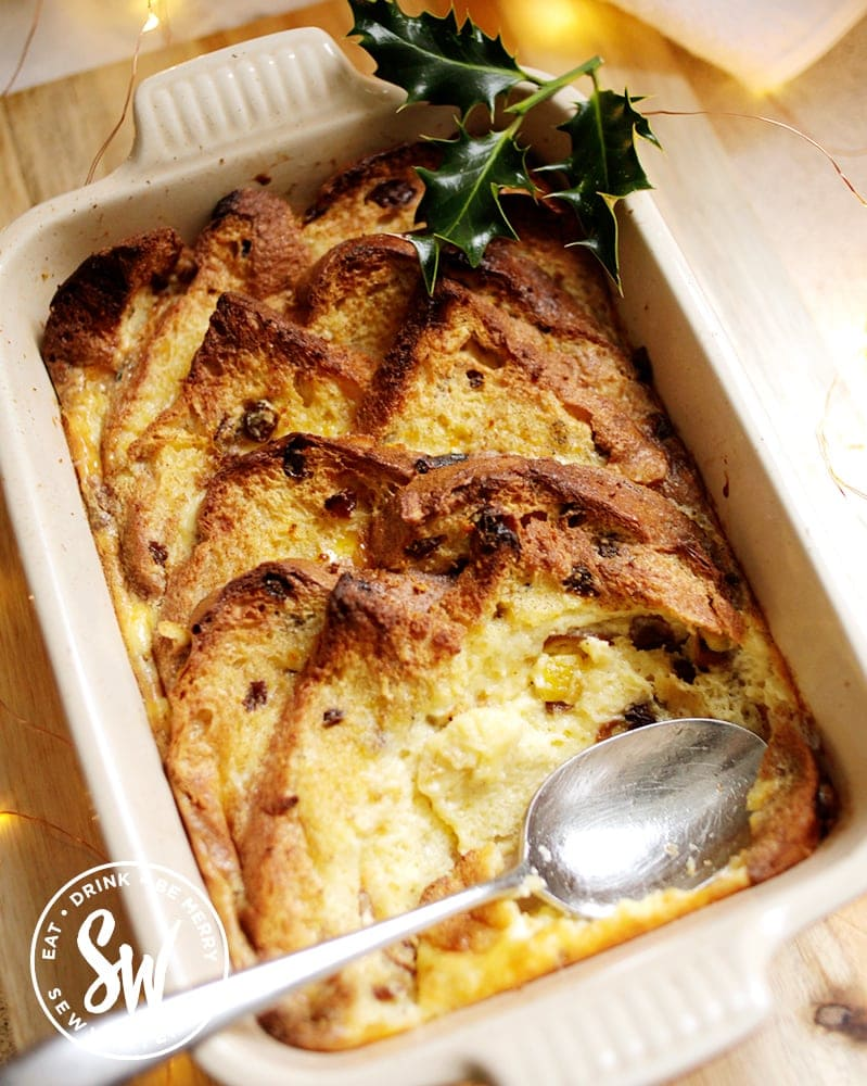 Panettone Bread and Butter Pudding in the Le Creuset dish ready to be served decorated with a sprig of holly.