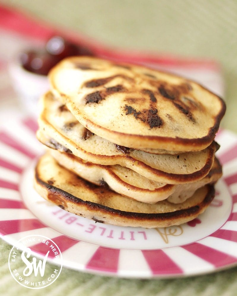 A golden brown stack of chocolate cherry pancakes on a pink stripe plate.