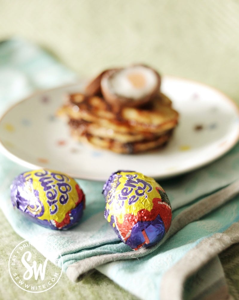 creme eggs in their wrapper next to a stack of creme egg pancakes