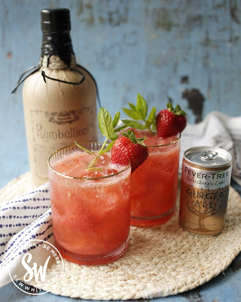 bright red and vibrant strawberry rum cocktail decorated with fresh mint and strawberry