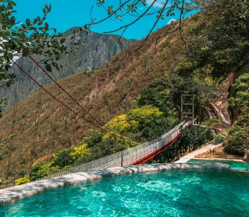 piscinas de agua azul con un puente al fondo - Visite Las Grutas Tolantongo