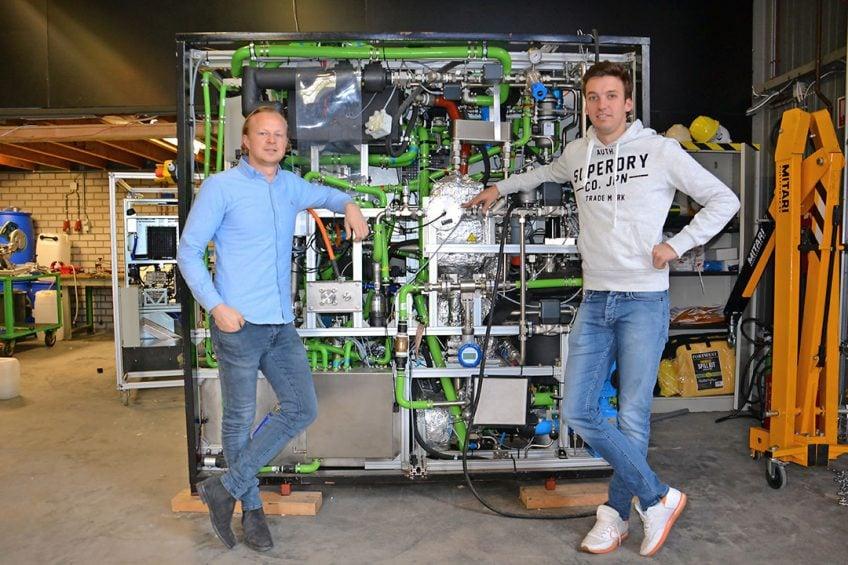 Links Max Aerts en rechts Tijn Swinkels van DENS, staand voor het prototype van hun systeem zoals het bedrijf dat bouwde voor een bus, in samenwerking met VDL. Dit prototype levert voldoende elektrische energie uit Hydrozine om een stadsbus aan te drijven.
