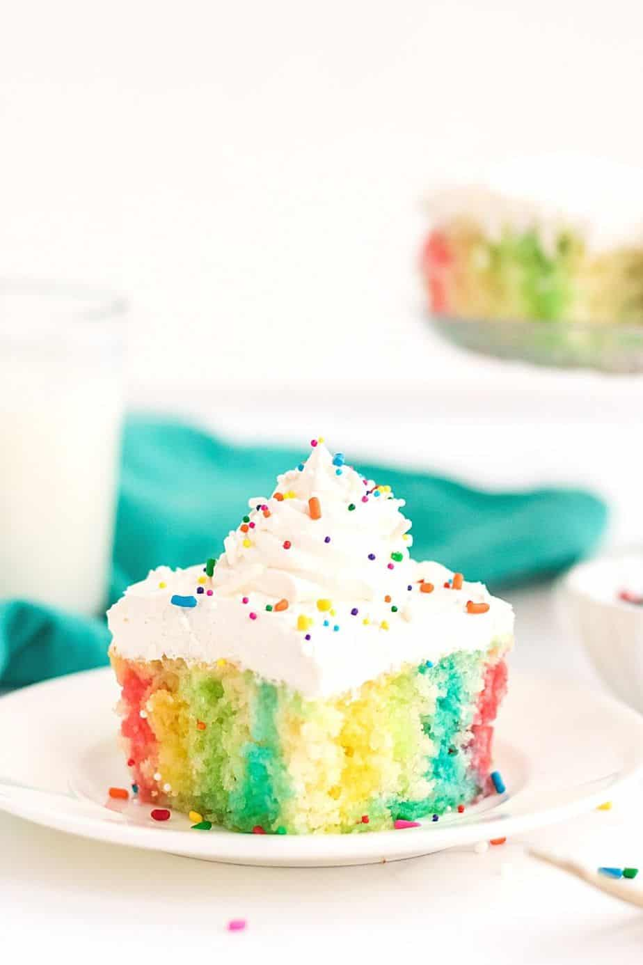 Make a colorful, moist, and utterly delicious cake within minutes with this Rainbow Poke Cake recipe. It is full of flavor and plenty of fun colors, including shades of pink, blue, and yellow!