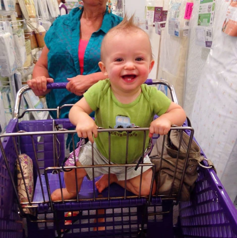 Baby boy in a purple buggy with a green shirt and a huge smile