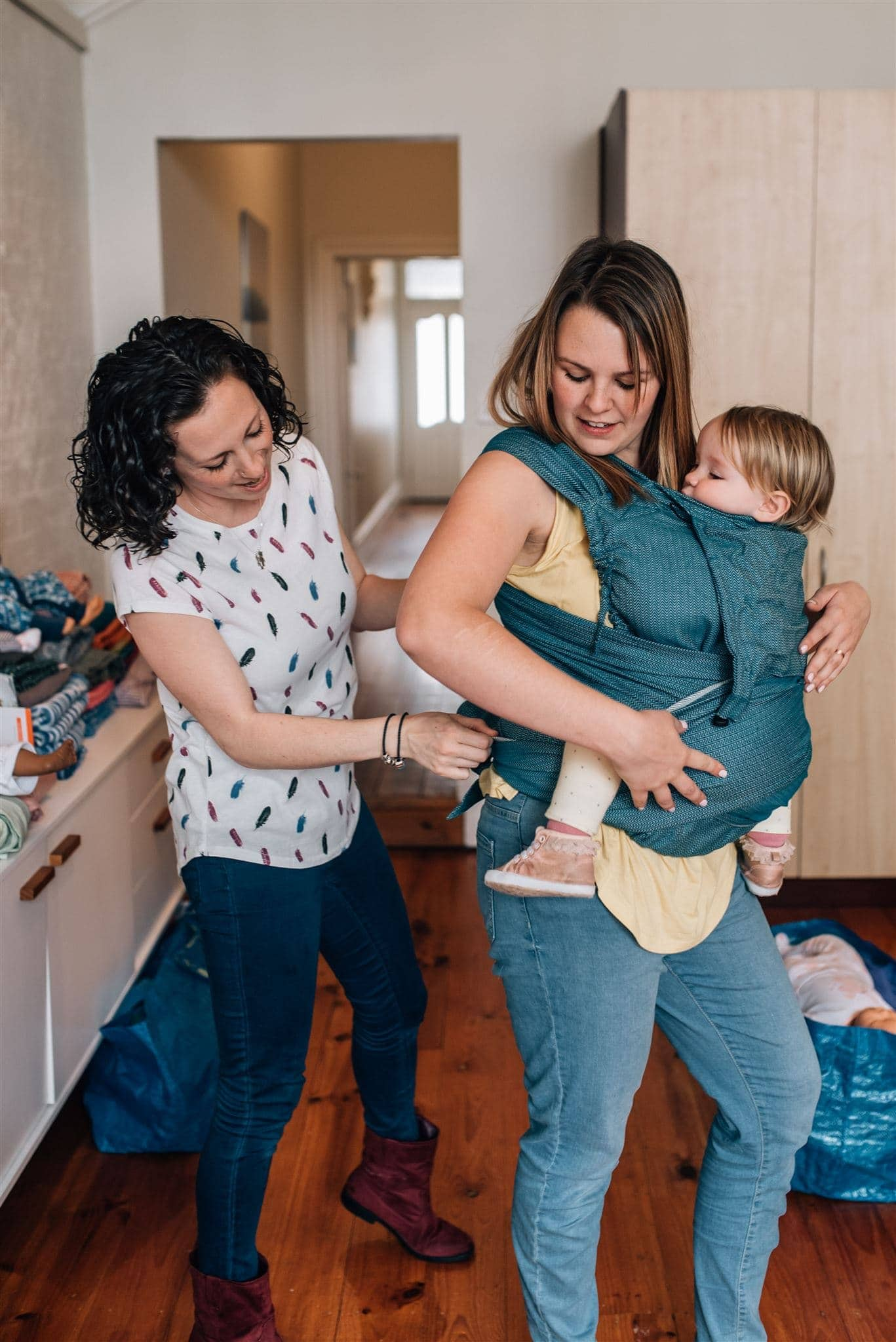 Babywearing consultant showing mother how to use a baby carrier
