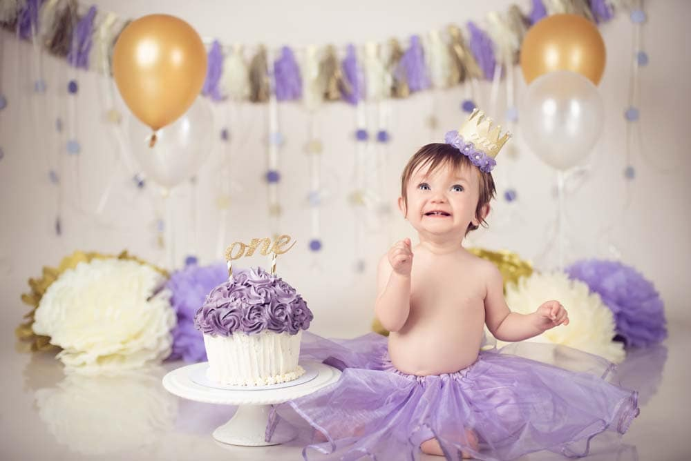 Baby girl in lilac tutu looking excited to see her first birthday cake
