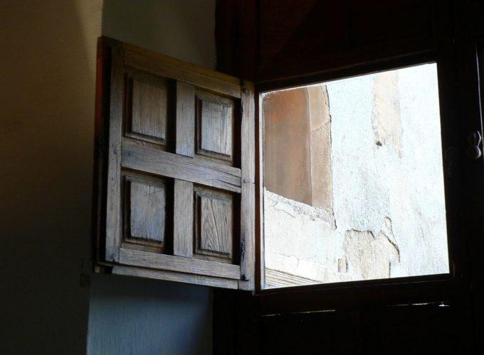 A window's wooden shutter is open