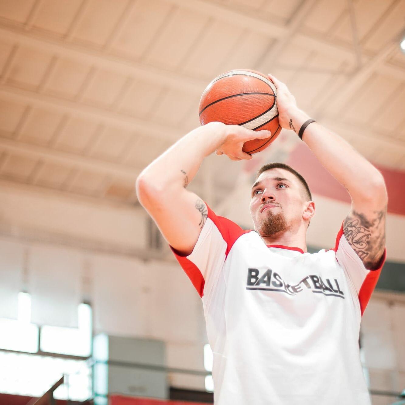 Man in white shirt shooting a basketball
